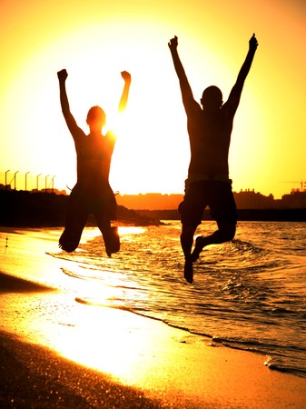 man jump: Two happy jumpers on the beach at sunset Stock Photo