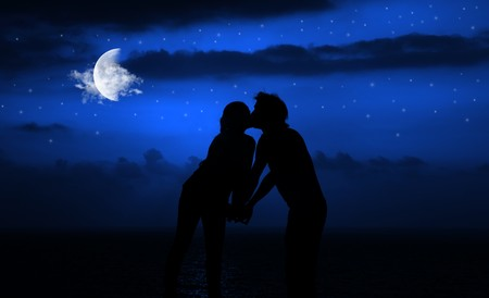 Happy couple romantically kissing at night under moonlight photo