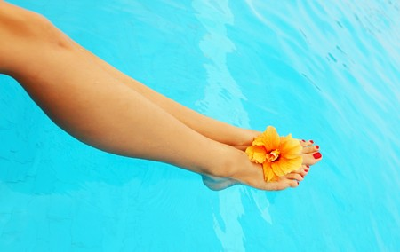 female legs: Beautiful female legs in the pool conceptual image of vacation Stock Photo