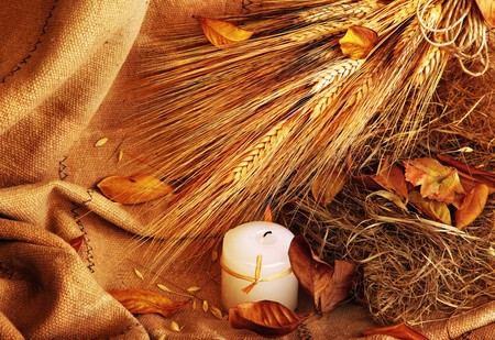 Grunge wheat background with autumn leaves & candle photo