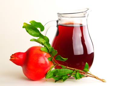 Pomegranate juice in a jug isolated on white photo