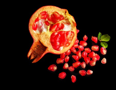 Red pomegranate isolated on black photo