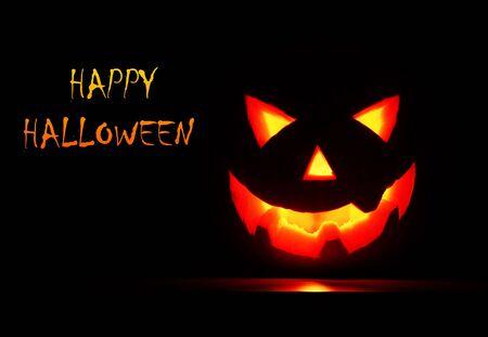 Glowing Halloween pumpkin isolated on black photo