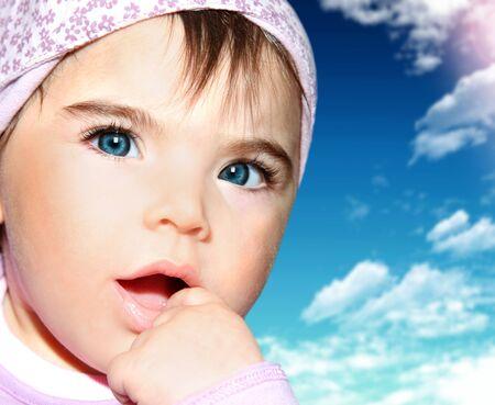 Little girl closeup portrait over blue sky photo