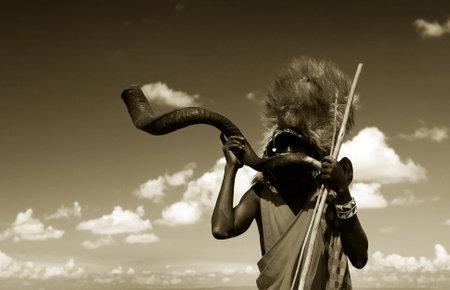 tribu: Guerrero Masai tocando bocina tradicional. Africa. Kenia. Masai Mara  Editorial