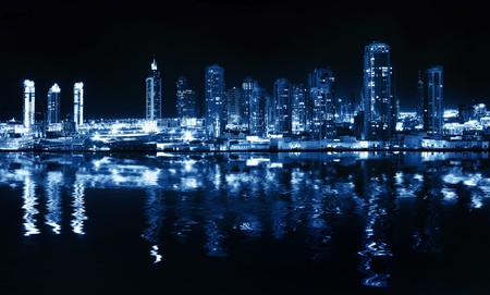 City at night, panoramic scene of downtown reflected in water, Dubai photo