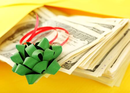Money as gift with green bow and yellow envelope photo