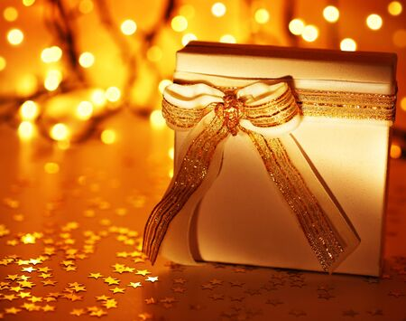 Gold holiday background with white present gift box, Christmas ornament and new year decoration over defocused lights photo