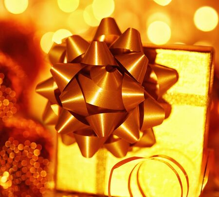 Golden holiday background with present gift box, Christmas ornament and new year decoration photo