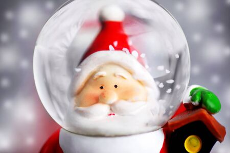 Santa Claus in the snow globe, closeup on Christmas ornament, decorative toy photo