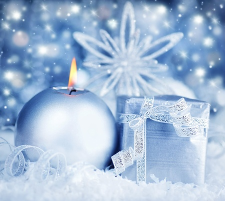 Winter holiday background with silver present gift box, candle ornament & Christmas snow decoration photo