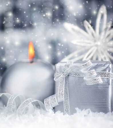 Winter holiday background with silver present gift box, candle ornament & Christmas snow decoration Stock Photo - 8267461