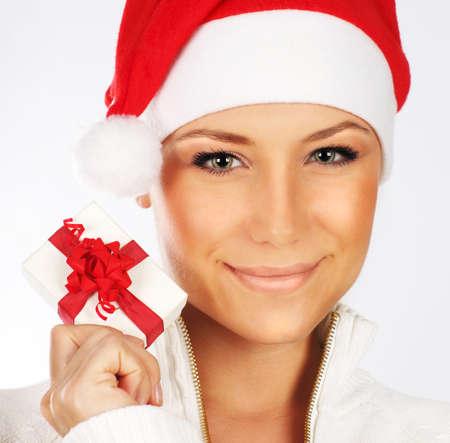 Pretty Santa girl closeup portrait, holding present gift box isolated on white background photo