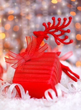 Christmas red gift box present as holiday background card with Christmas tree deer ornament & defocus lights decoration photo