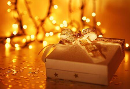 Fondo de oro de vacaciones con blanco presente caja de regalo, ornamentos de Navidad y año nuevo decoración sobre luces defocused