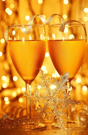 Romantic holiday dinner, celebration of Christmas or new year eve, party with Champagne and festive gold ornament decoration photo