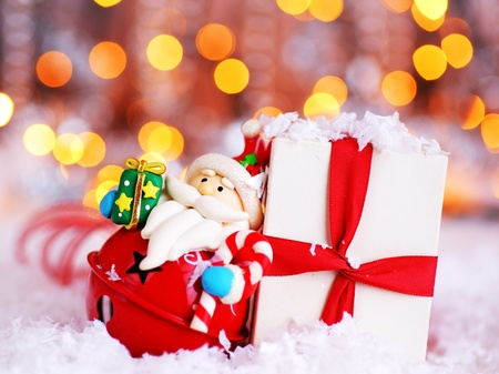 Holiday background with cute Santa Claus Christmas tree decorative ornament & gift box in snow over abstract defocus lights Stock Photo - 8323872