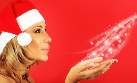 Portrait of pretty Santa girl blowing a kiss with snowflakes, isolated on red winter holiday background photo