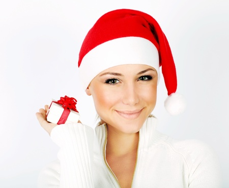 holding a christmas ornament: Pretty Santa girl closeup portrait, holding present gift box isolated on white background