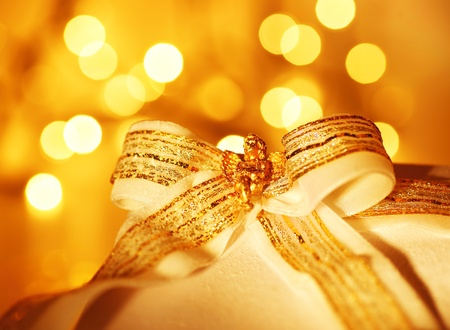 Gold holiday background with white present gift box, Christmas ornament and new year decoration over abstract defocused lights Stock Photo - 8375788