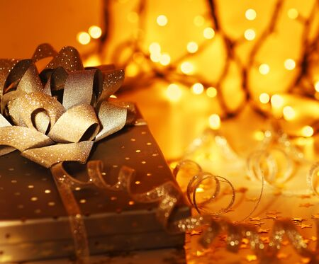Shiny Christmas gift box , ornament & holiday decoration over abstract  golden lights background Stock Photo - 8375810