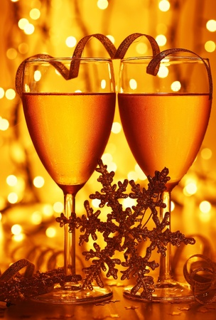 Romantic holiday drink, celebration of Christmas or new year eve, party with Champagne and festive gold ornament lights decoration Stock Photo - 8375910