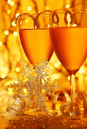 Romantic holiday drink, celebration of Christmas or new year eve, party with Champagne and festive gold ornament lights decoration