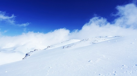 Winter landscape of high mountains with snow blizzard and fresh blue sky, beautiful nature panoramic background photo
