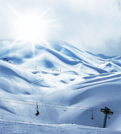 Winter mountain ski resort, landscape with snow, sunny sky and chairlift photo