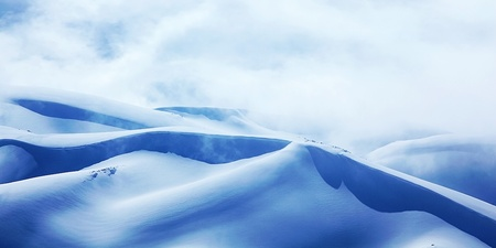 Winter landscape of high mountains with snow blizzard and fresh blue sky, beautiful nature panoramic image photo
