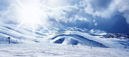 Winter mountain ski resort panoramic landscape with snow, sunny sky and chairlift photo