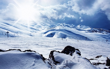 Winter mountain ski resort panoramic landscape with snow, sunny sky & chairlifts photo