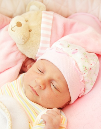 Cute little baby sleeping in pink pajama with teddy bear toy Stock Photo - 8570549