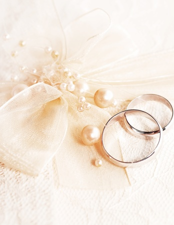 Pair of golden wedding rings over invitation card decorated with silk bow & pearls Stock Photo - 8570574