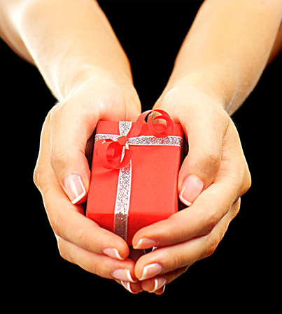 Beautiful red gift box with female hands isolated on black background photo