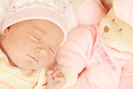 Cute little baby sleeping in pink pajama with teddy bear toy photo