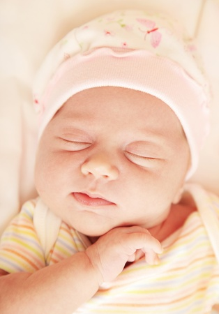 Closeup portrait of cute little baby sleeping in pink pajama & hat photo