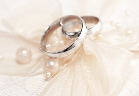 proposal of marriage: Pair of golden wedding rings over invitation card decorated with silk bow & pearls