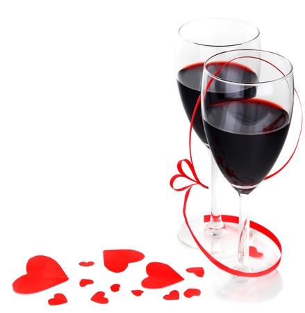 Bebida de vacaciones románticas, celebración de San Valentín, vino tinto con decoración ornamento & la cinta de opciones de corazones, aislado en fondo blanco