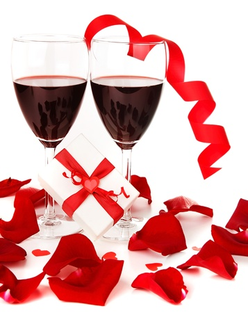 Romantic holiday gift, celebration with red wine with hearts ornament & ribbon decoration over white background photo