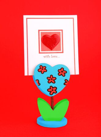 Blank card with red heart & flower holder isolated on red background, conceptual image of love & Valentines day holiday photo