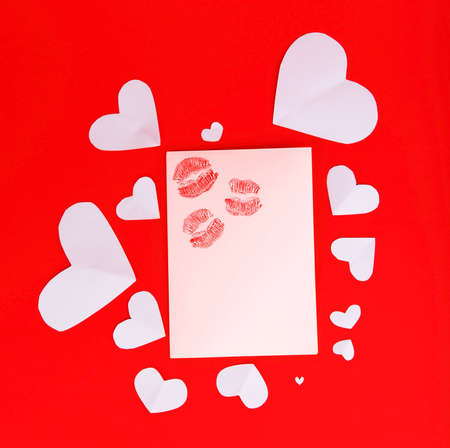 Blank card with red kisses isolated on red background, conceptual image of love & Valentines day holiday photo