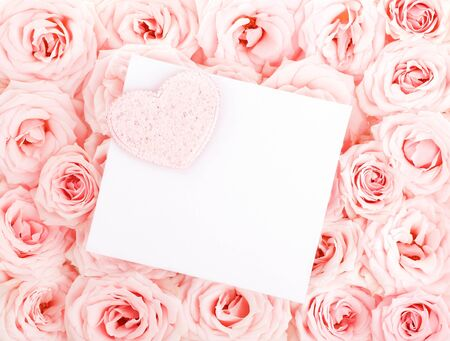 Pink fresh roses background with red heart & isolated  blank greeting card, love concept  photo