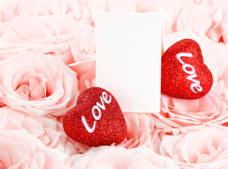 two object: Pink fresh roses background with red hearts & blank greeting card, love concept