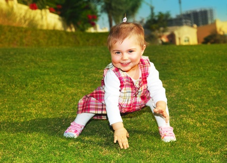 Sweet baby girl playing outdoor on the green grass Stock Photo - 8876023