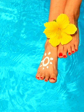 Beautiful female legs with flower in the pool conceptual image of vacation Stock Photo - 8876732