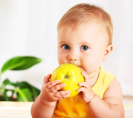 Little baby eating apple, closeup portrait, concept of health care & healthy child nutrition
