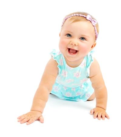 Adorable petite fille bébé en riant, rampant & jouant dans le studio, isolé sur fond blanc