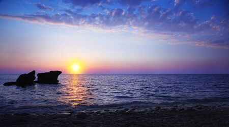 Beautiful sunset on the beach, seascape with calm ocean and rocks in the blue water photo