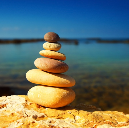 white stone: Zen spa balance stones, over blue calm sea background, conceptual image of relaxation & vacation Stock Photo